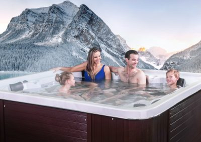 A family in an Arctic Spa with a snow capped mountain and lake in the background